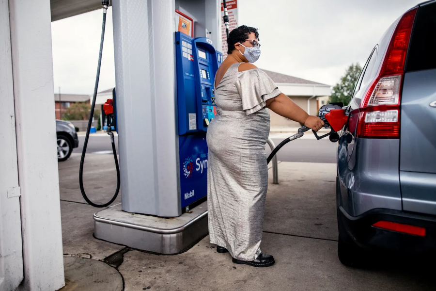 Professor Sami Schalk wearing a floor length silver dress, a silver sequin face mask, filling up a vehicle's gas tank at a gas station.