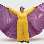Sami Schalk wears a yellow jumpsuit and a shiny purple cape. Her arms are open to show the fullness of the cape.