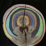 Drawing of a body at the center of multi-colored tree rings, black background.
